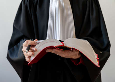 Justice, lawyer holding open red law book
