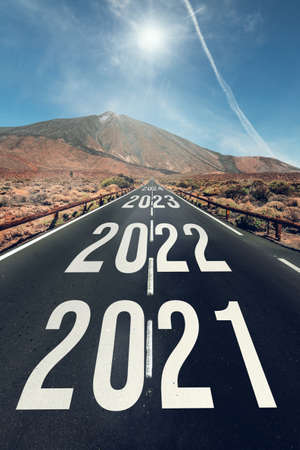 2021 to 2025 written on the asphalt road surrounded by a mountain landscape and a beautiful blue sky.