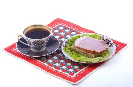 一杯のコーヒーと赤いナプキンのサンドイッチ プレート。白背景