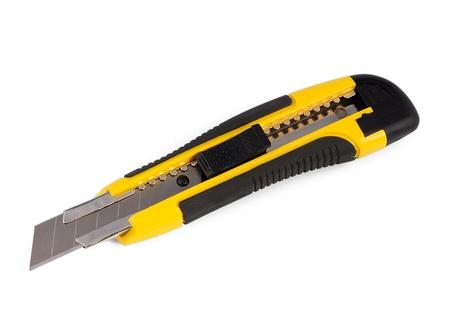白い背景の上の黄色の文房具のナイフ