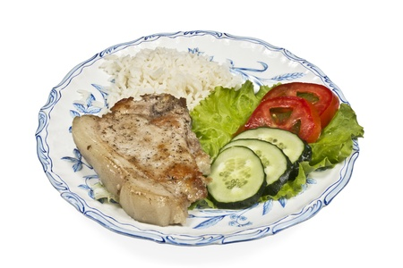 肉と野菜と米白い皿の上