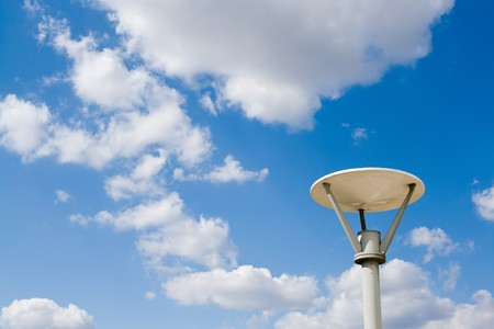 Street lamp against the blue sky with clouds photo