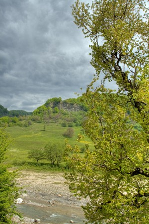 Storm approaching over eroded hill and river