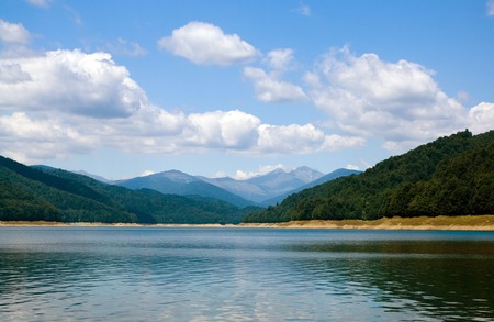 clouds above lake and trees on coast, distant mountains are showing their tops Stock Photo