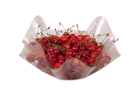 Cherries in a wavy glass bowl isolated on white background
