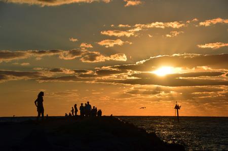 これは、メキシコ湾の桟橋から夕日を見て女性 (と群衆) の写真 写真素材
