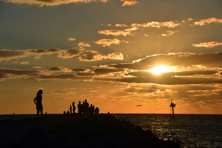 greys: This is a photo of a lady (and crowd) watching the sunset from a Gulf of Mexico jetty