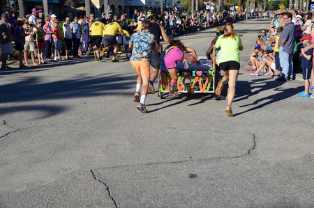VENICE, FL - OCTOBER 18:  Competitors pushing a bed while a team mate jumps on it during the 11th Annual Venice Sun Fiesta bed race on October 18, 2014 in Venice FL