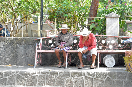 SANTIAGO, GUATEMALA - JULY 1, 2015:  Two unknown, elderly Guatemalan men, dressed in traditional clothing have a conversation on a local park bench. Editorial