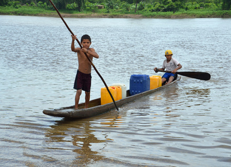 nicaraguan: WIS WIS VILLAGE, NICARAGUA - JULY 8, 2015:  Two unknown Nicaraguan boys paddle and pole their ponga to shore after retrieving drinking water for the family.  This villiage is located on the Rio Coco and not accessible by road.  All movement to and from th