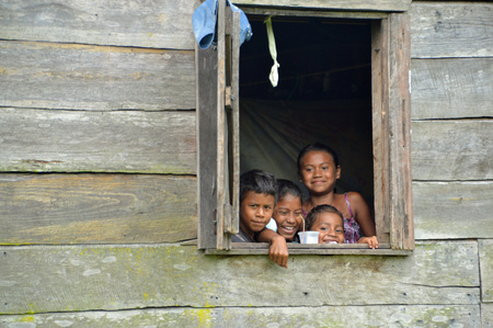 SAUPUKA, NICARAGUA - JULY 8, 2015:  Three unknown Nicaraguan girls and one unknown Nicaraguan smiling from the window of their home as the rare tourist passes by. Editorial