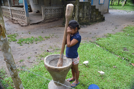 WIS WIS VILLAGE, NICARAGUA - JULY 8, 2015:  An unknown Nicaraguan girl hides her eyes as she plays hide and seek.  This village along the Rio Coco is unaccessible by road and the rare tourists arrive by boat.