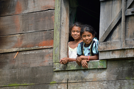 unknown age: SAUPUKA, NICARAGUA - JULY 8, 2015: Two school age, unknown Niaraguan girls looking outside from their house window, as I, the rare tourist passes by. Editorial