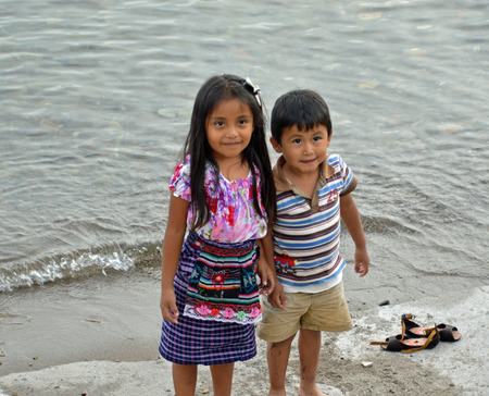 PANANACHEL GUATEMALA - JULY 4, 2015:  An unknown Guatemalan prescheool aged girl and her younger brother play along the banks of Lake Atitlan.
