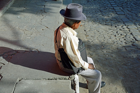 ANTIGUA, GUATEMALA - JUNE 26, 2015; An unknown elderly Guatemalan man takes a break from the hectic pace of the local market