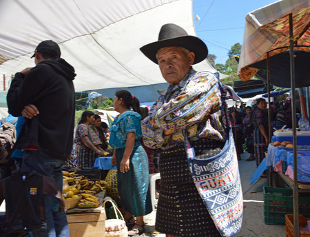 ANTIGUA, GUATEMALA - JULY 3, 2015; An traditionally dressed, unknown elderly Guatemalan man stops to look at a tourist me with a camera.  With the size of the crowds at this local market, tourists are a rare find.