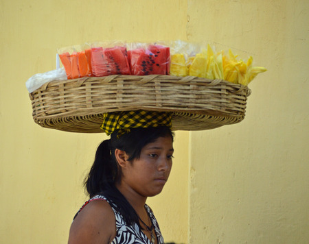 ANTIGUA, GUATEMALA - JUNE 27, 2015; An unknown, young Guatemalan woman carries sliced fruit in a basket on her head.  She walks the local streets selling to locals and tourists. Editorial