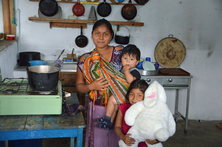 guatemalan: SAN PEDRO, GUATEMALA - JUNE 30, 2015; An young Guatemalan woman, prepares a stew while holding one of her children.  Her older daughter is playing with her large stuffed rabbit.  Names and ages are unknown.