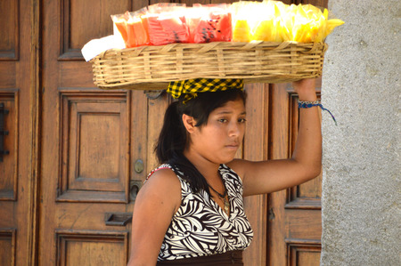 local 27: ANTIGUA, GUATEMALA - JUNE 27, 2015; An unknown, young Guatemalan woman carries sliced fruit in a basket on her head.  She walks the local streets selling to locals and tourists. Editorial