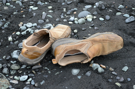 A pair of brown shoes on a black sand beach in Iceland