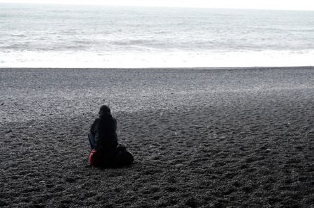 A lone hiker taking a break on a black sand beach on the North Atlantic Ocean in Iceland