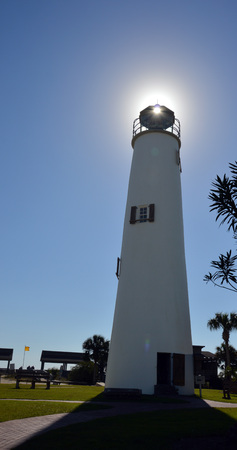 A photo of a lighthouse with the sun shinning through the lens Stock Photo