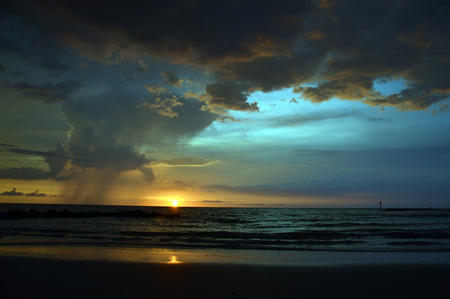 A sunset from the beach with storm clouds and rain in the distance Stock Photo