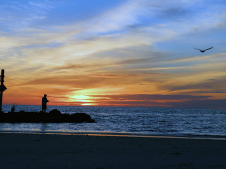 Fisherman casting in the Gulf of Mexico during sunset Stock Photo