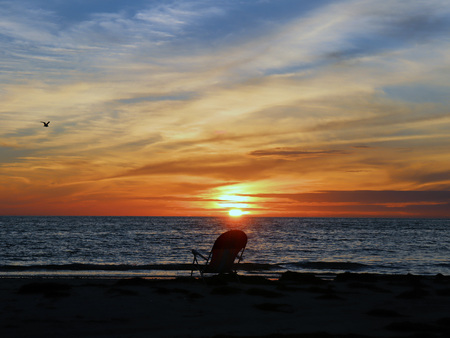 A chair faces the sun setting over the Gulf of Mexico