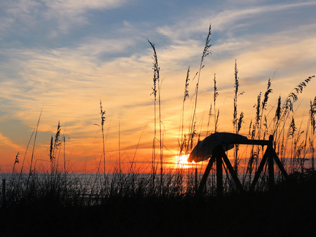 Sunset over the Gulf of Mexico with seagrass and umbrella in the foreground Stock Photo