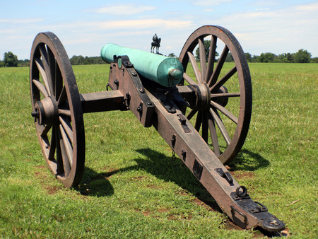 Civil war cannon with man on a horse in the background