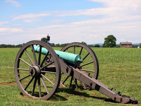 Civil war cannon with house and man on a horse in the background