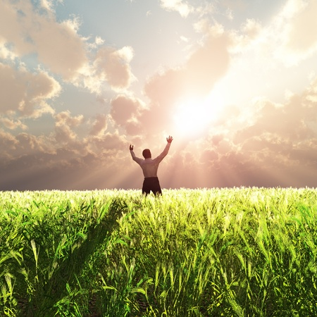 manos orando: hombre en campo de trigo al amanecer