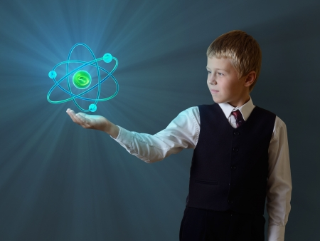 schoolboy holding glowing atom photo
