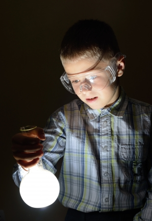 schoolboy holding glowing bulb Stock Photo - 15787192