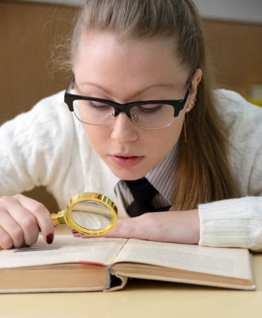 woman reading a book with a magnifying glass Stock Photo - 16401559