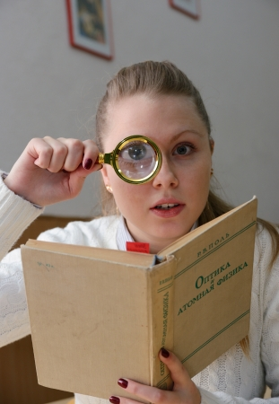 woman reading a book with a magnifying glass photo