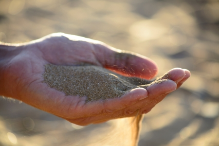 disseminate: sand pours out of the hands Stock Photo