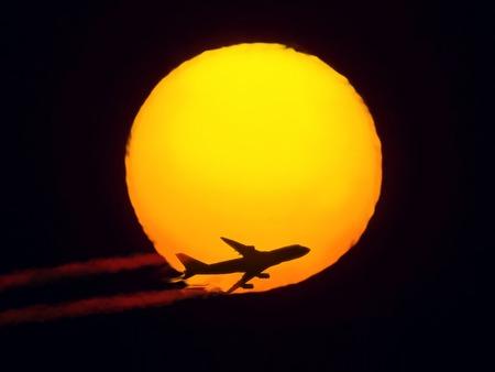 plan éloigné: aéronefs volant à travers le soleil