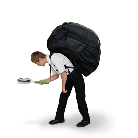 difficult to find: schoolboy carries a backpack and magnifying glass