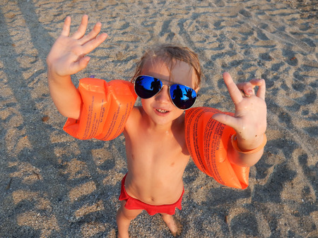 armbands: funny girl in sunglasses on summer beach