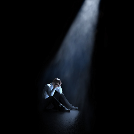 lonely man sitting in a dark room