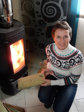 wood stove: Woman puts wood in fireplace Stock Photo