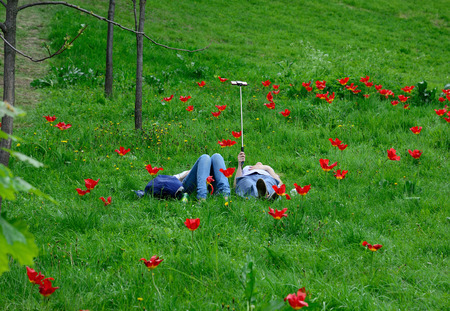 people relaxing: couple makes the selfie lying on flower field Stock Photo