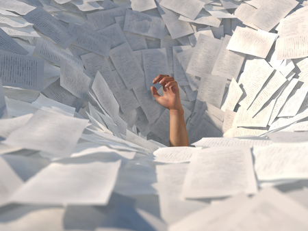 hand drowning in paper sheets Stock Photo