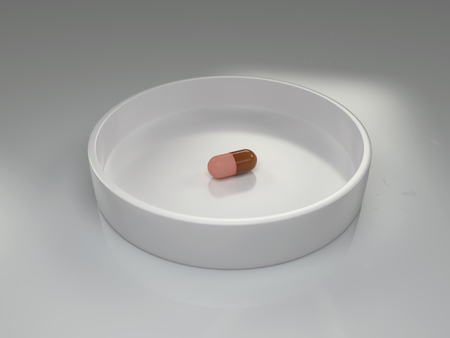 one capsule in a white laboratory dish