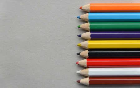 palette of colored pencils on gray cardboard