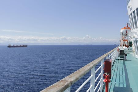The long deck of the ship, beautiful scenery and a huge tanker drifting into the sea. Banque d'images - 145742055