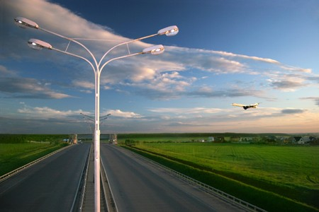 Airplane flying over highway photo
