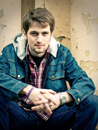 Young man wearing jeans clothes sits in front of the cracked wall. Фото со стока